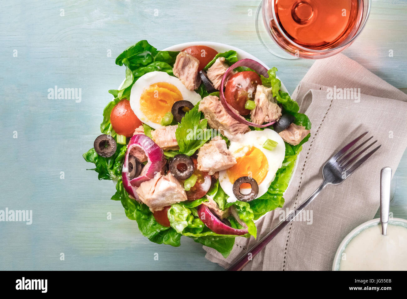 Overhead photo of a plate of salad with canned tuna, boiled eggs, green lettuce leaves, onions, black olives, and - Stock Image