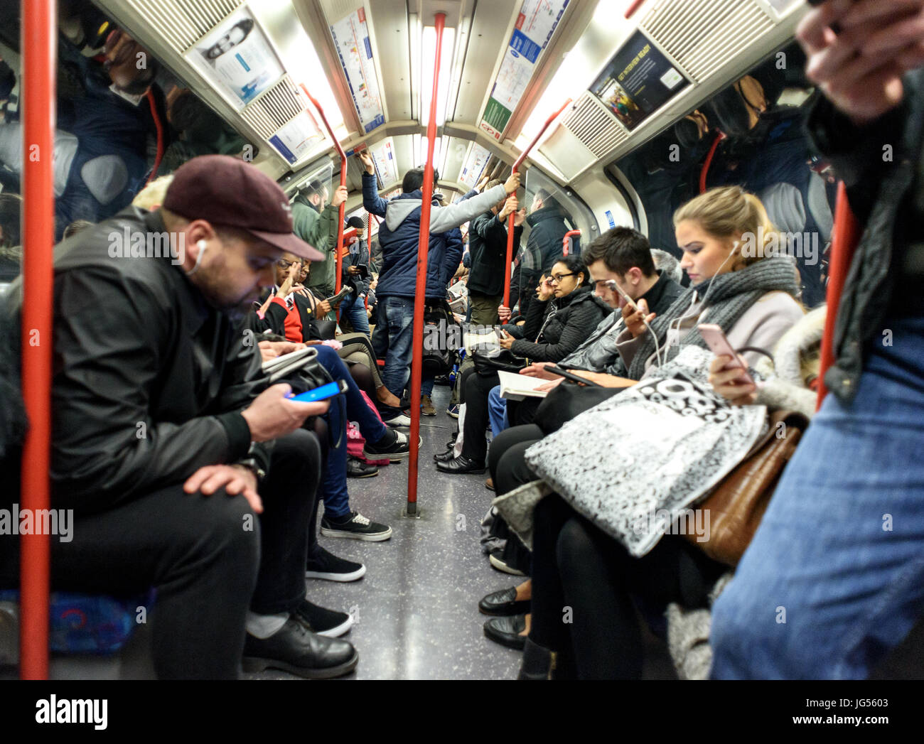 Various mixed people riding on a London Underground tube train in their carriages both sitting and standing - Stock Image