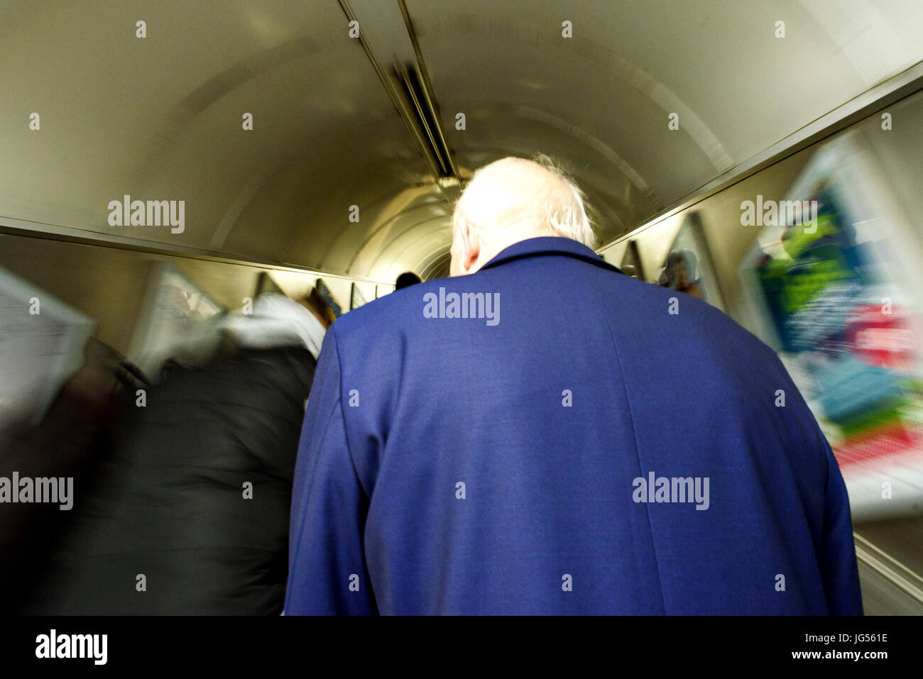 An old man with white hair and blue coat on a London underground escalator with motion blur - Stock Image