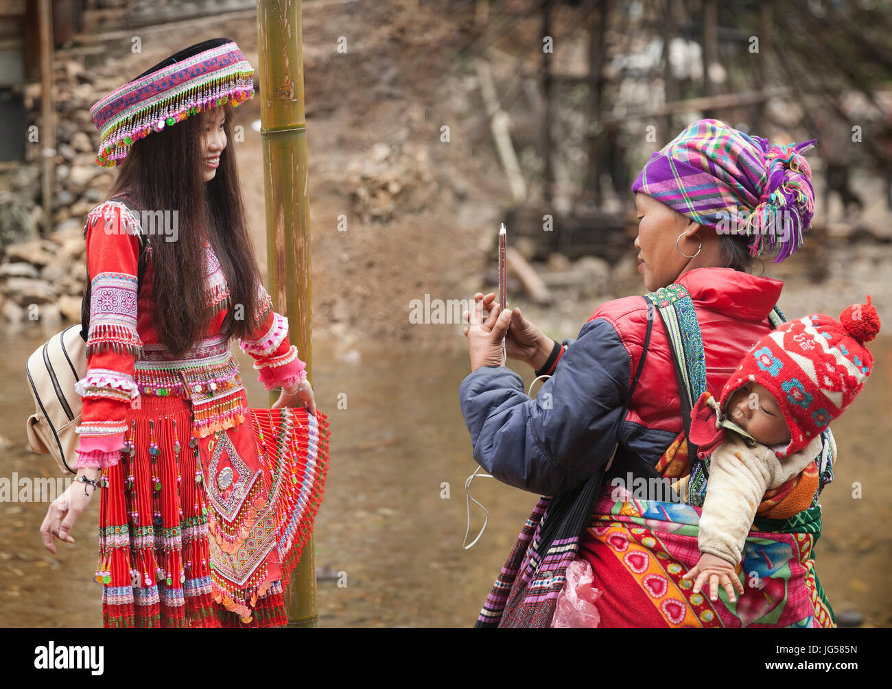 Hilltribe traditional attire, Cat Cat village at Sapa in Lao Cai, Vietnam, village member uses a smart phone to - Stock Image