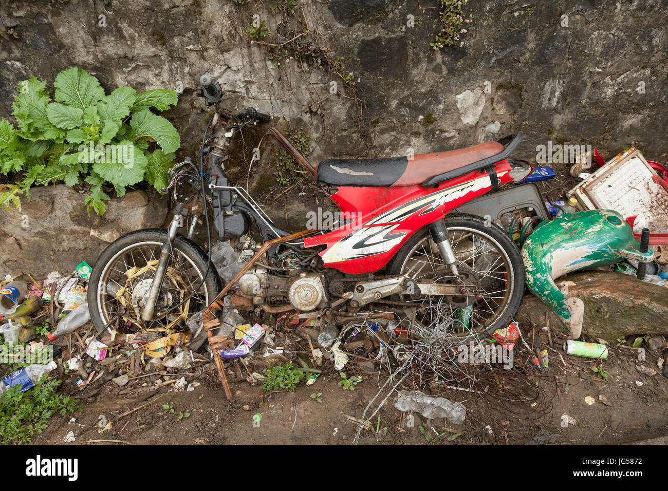 Rubbish including an old motorbike discarded in a roadside ditch, Vietnam. - Stock Image