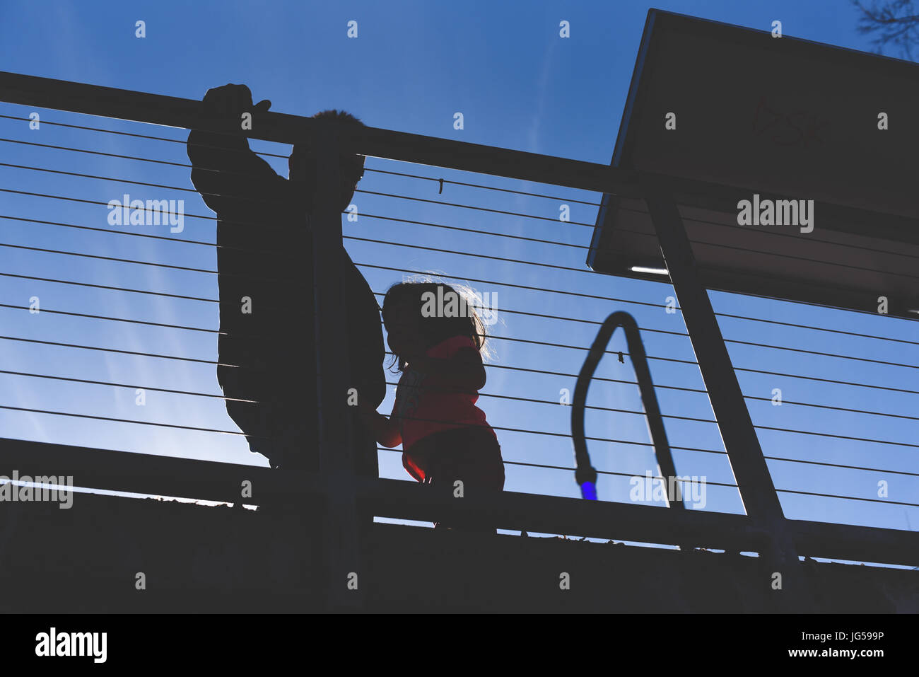 A little girl with her father silhouetted and looking up - Stock Image