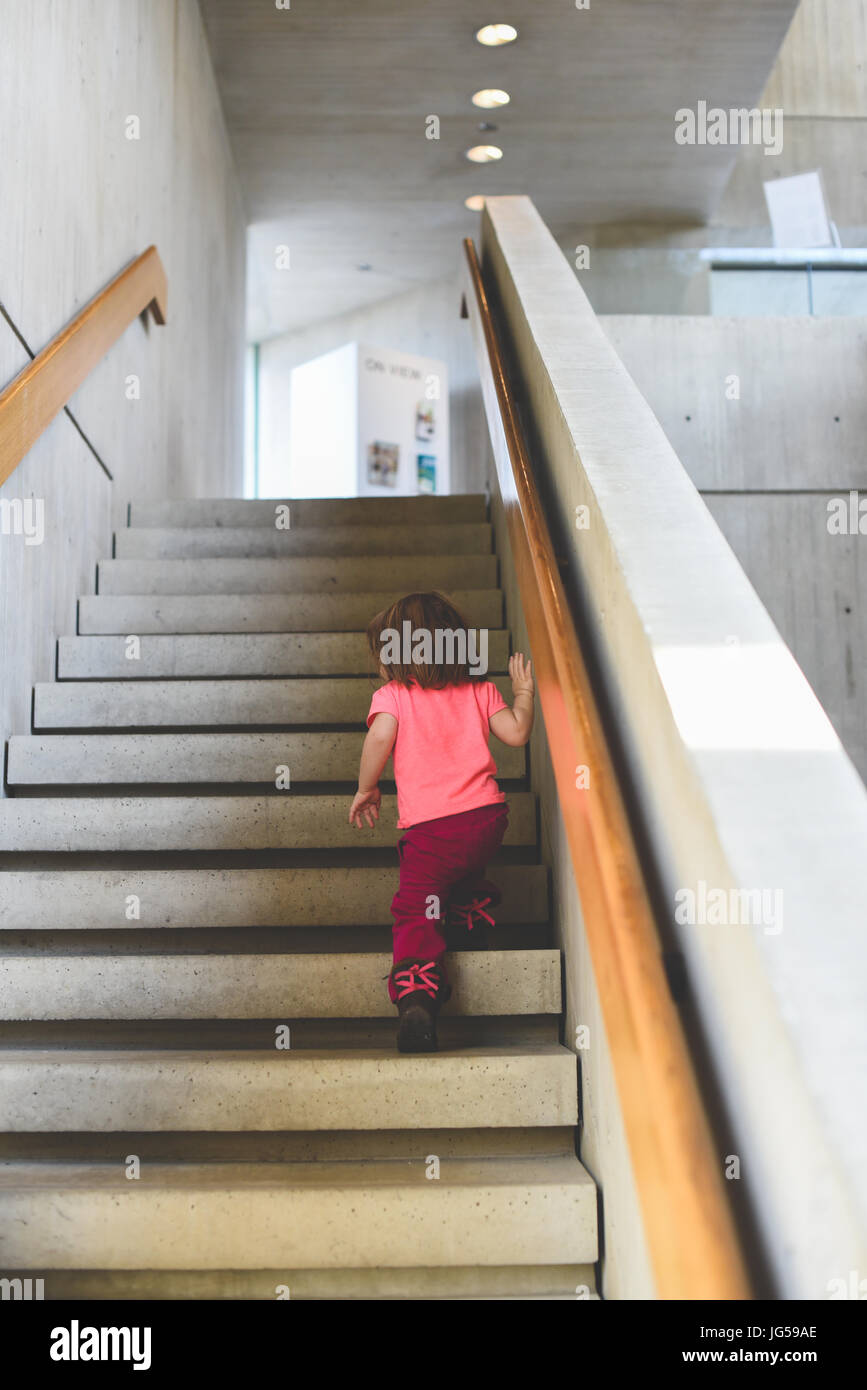 A little girl climbs a flight of stairs in an art gallery. - Stock Image