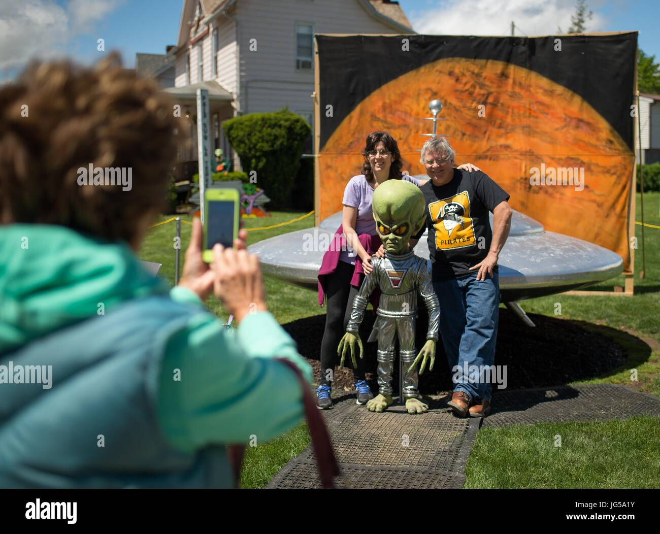 Visitors have their photo taken in front of an alien statue and sculpture of a UFO set up for the Mars New Years - Stock Image
