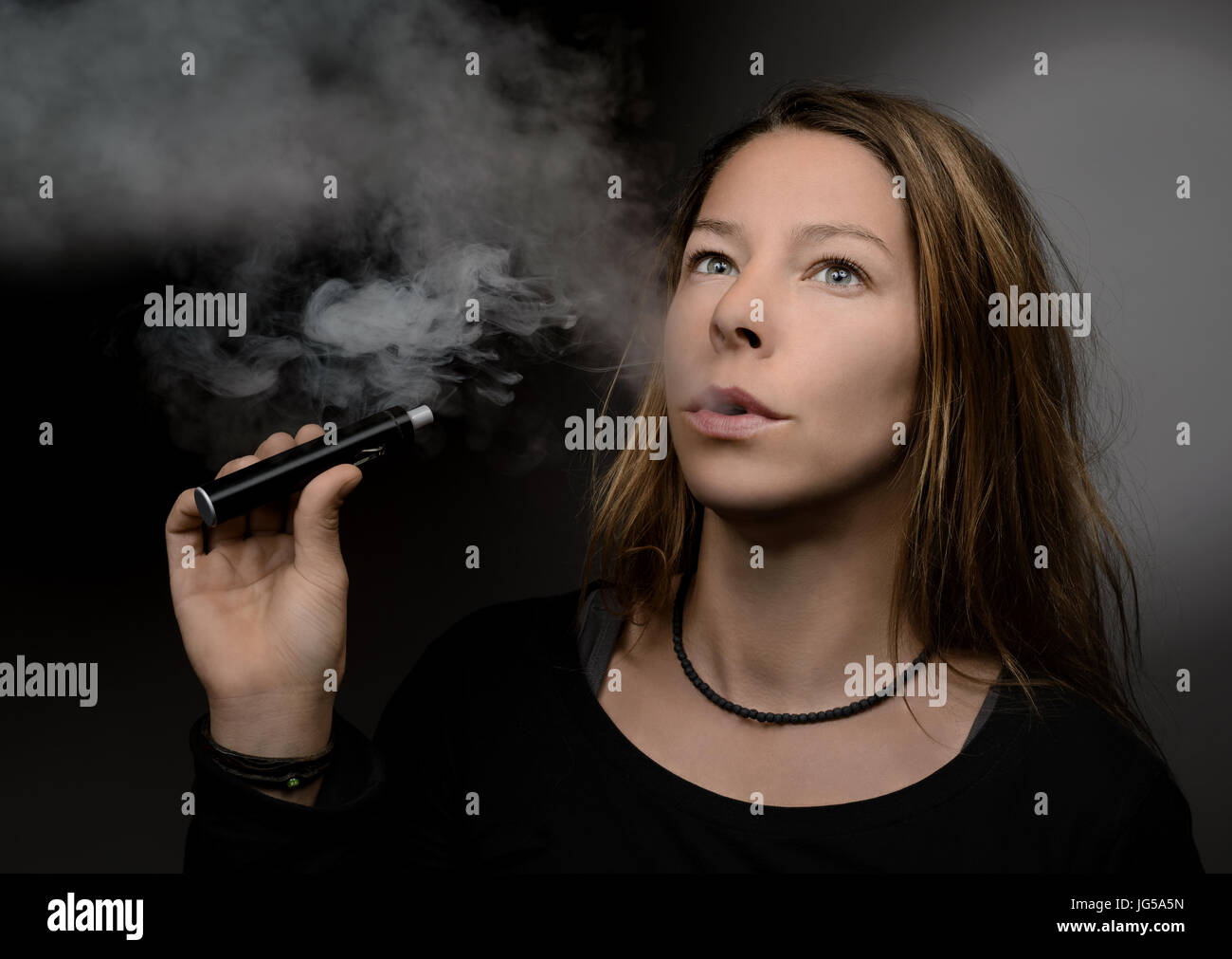 Woman smoking an electro cigarette - Stock Image