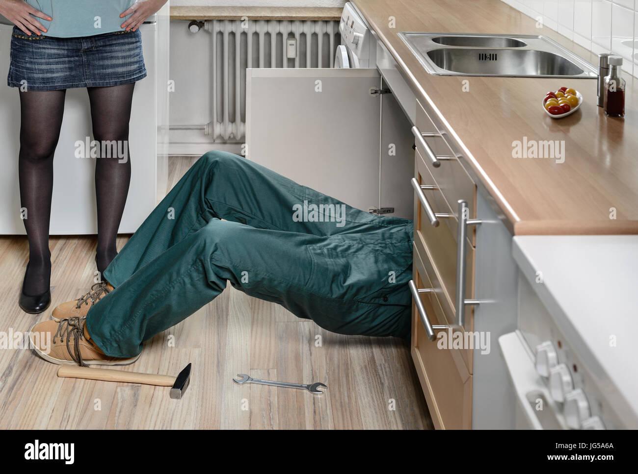 Plumber installer service reparing kitchen sink installation - Stock Image