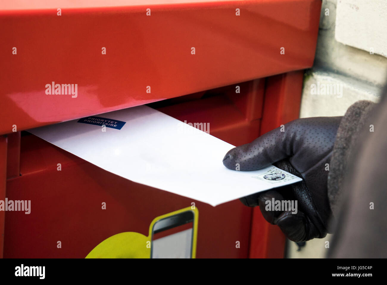 Sending a letter. Putting it to the red post box - Stock Image