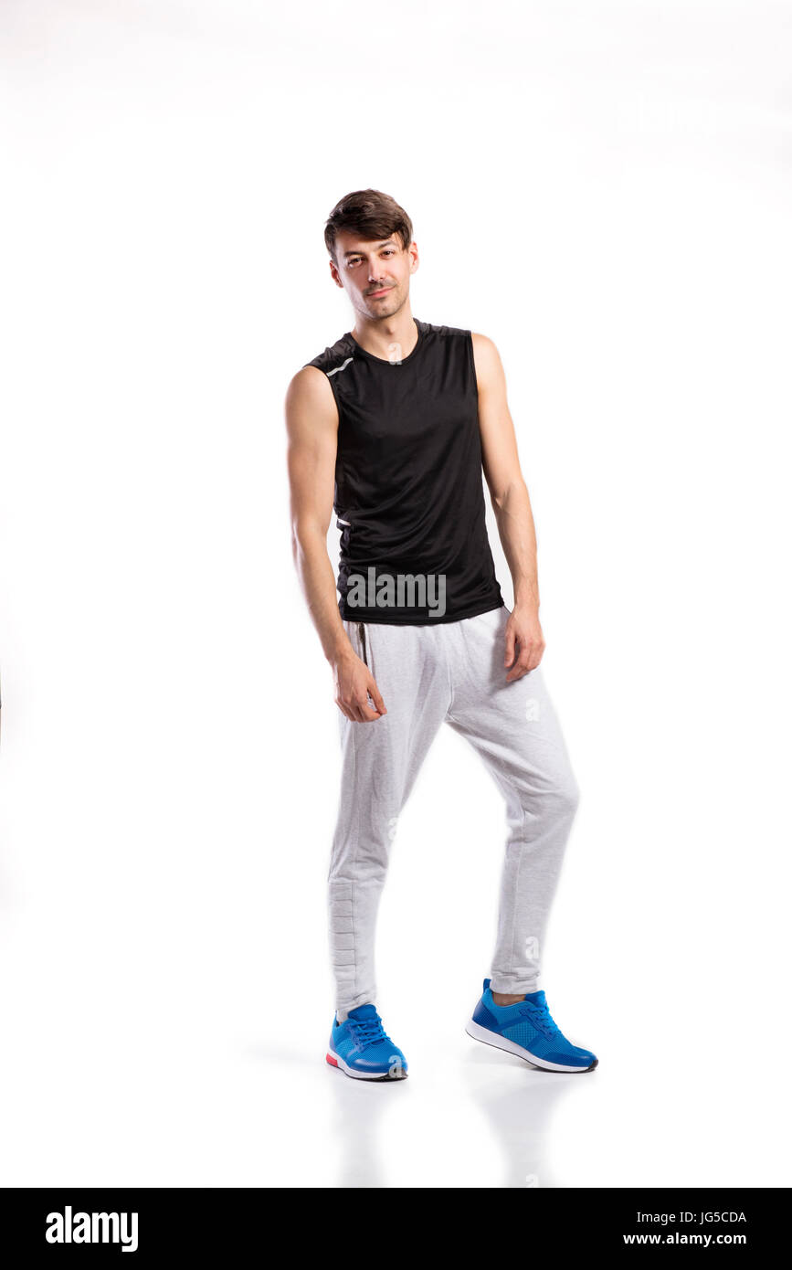 eb0e00465857c Handsome hipster fitness man in white tank top shirt and gray sweatpants. Studio  shot on