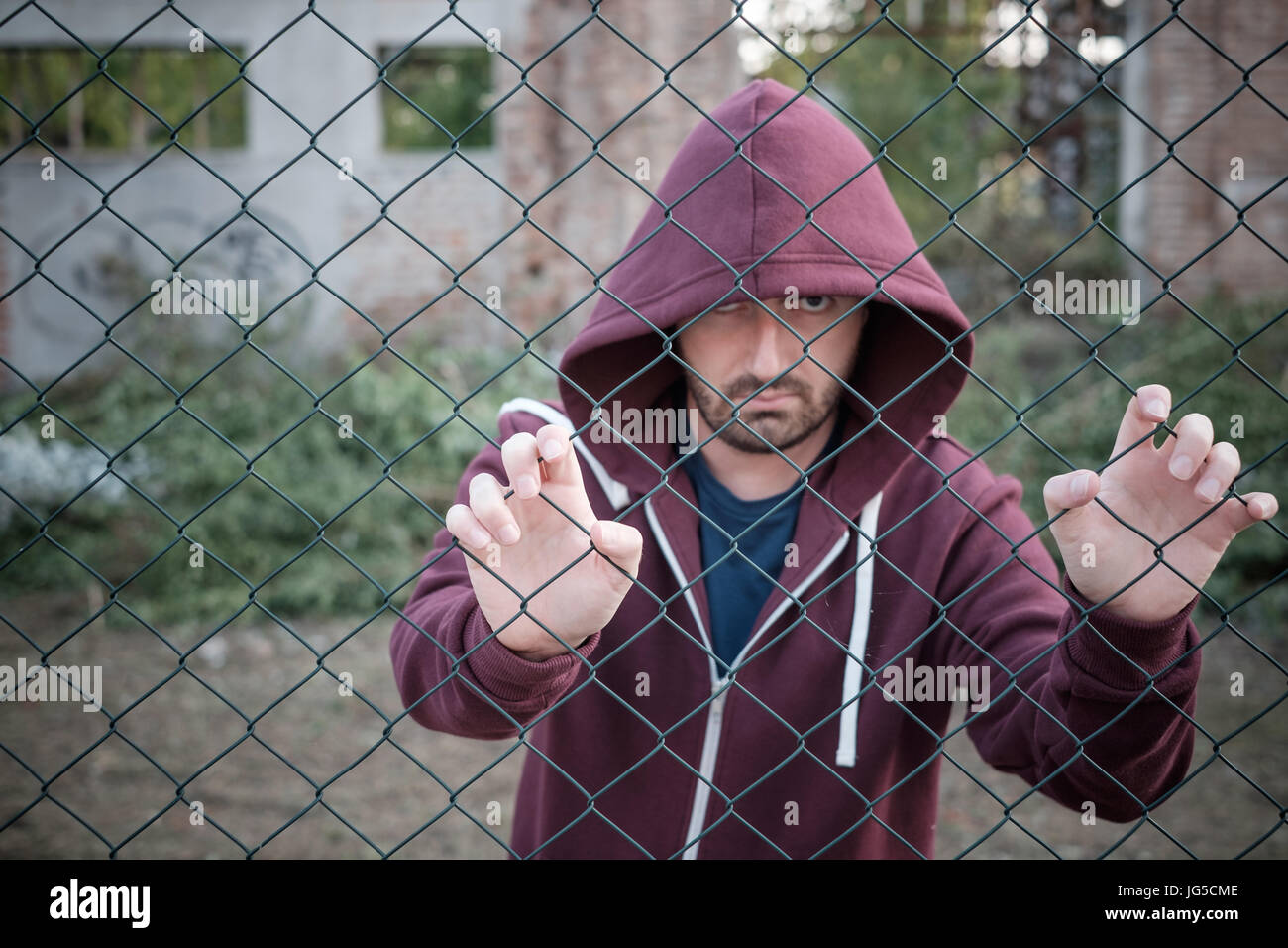 Sad and troubled boy against metal fence - Stock Image