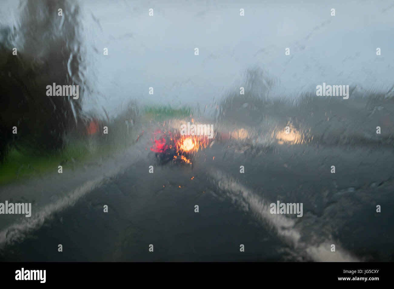 Driving with heavy rain on car windscreen on State Highway 1, Auckland, New Zealand, NZ - car in front is indicating - Stock Image