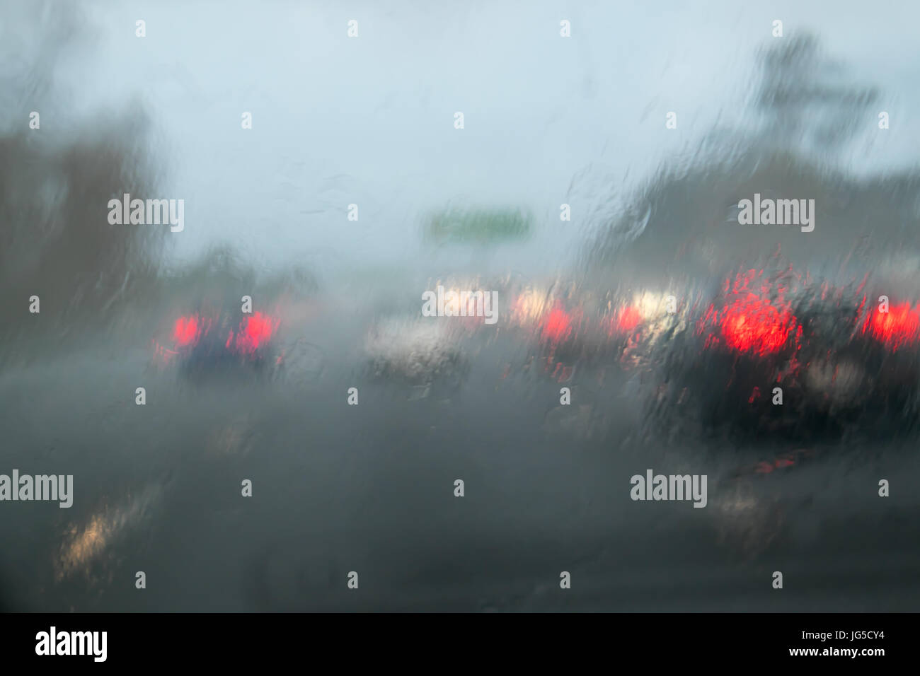 Driving with heavy rain on car windscreen on State Highway 1, Auckland, New Zealand, NZ - car in front does not - Stock Image