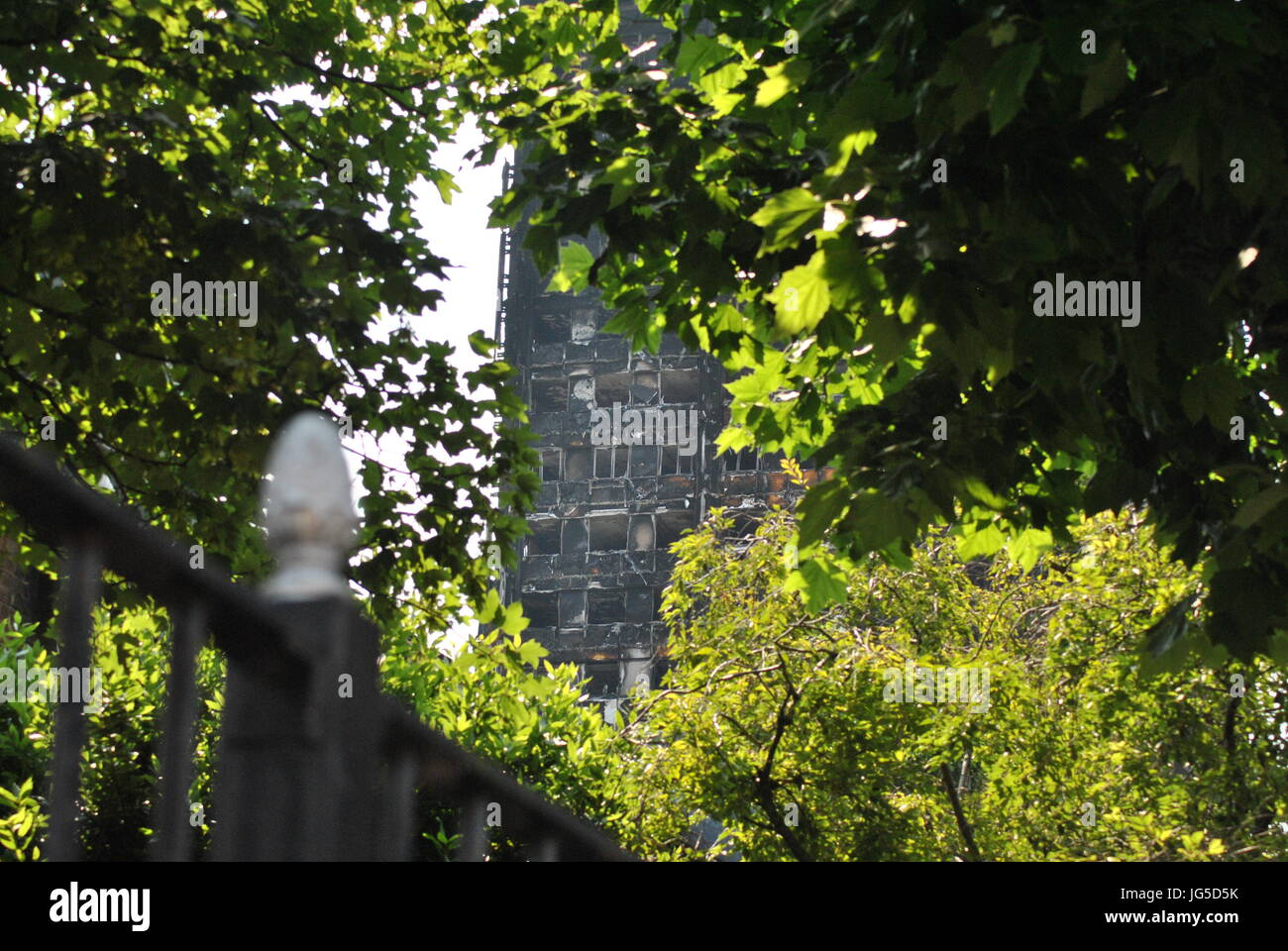 Grenfell Tower Fire, Leafy View Through to Burned Remains of Building, 14th June, 2017. Grenfell erupted in flames, - Stock Image