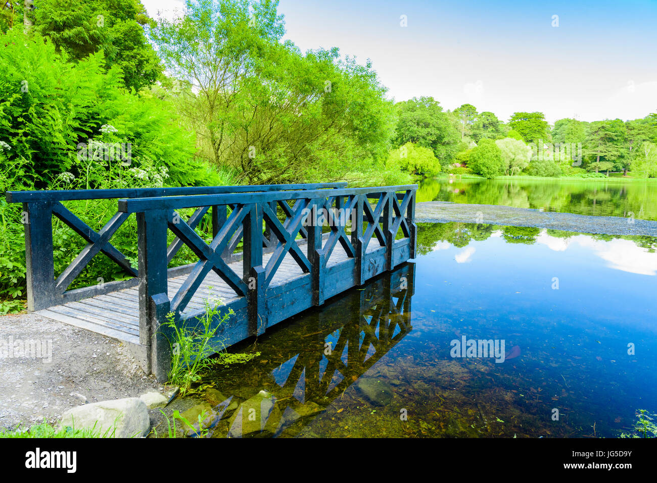 Small pier leading over a lake on a sunny day. - Stock Image