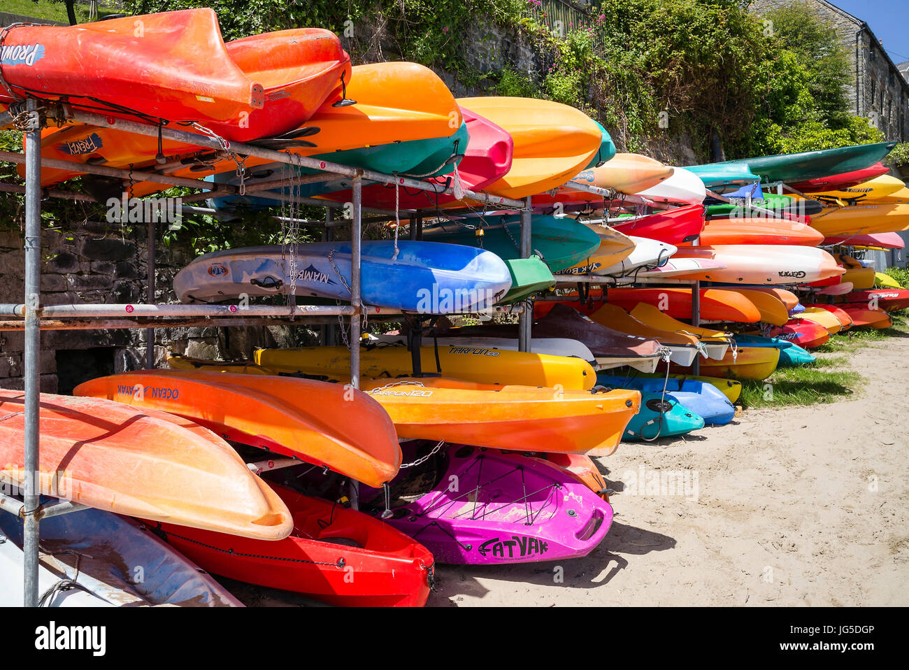 An eye-catching store of kayaks in New Quay Harbour Ceredigion, Wales, UK - Stock Image