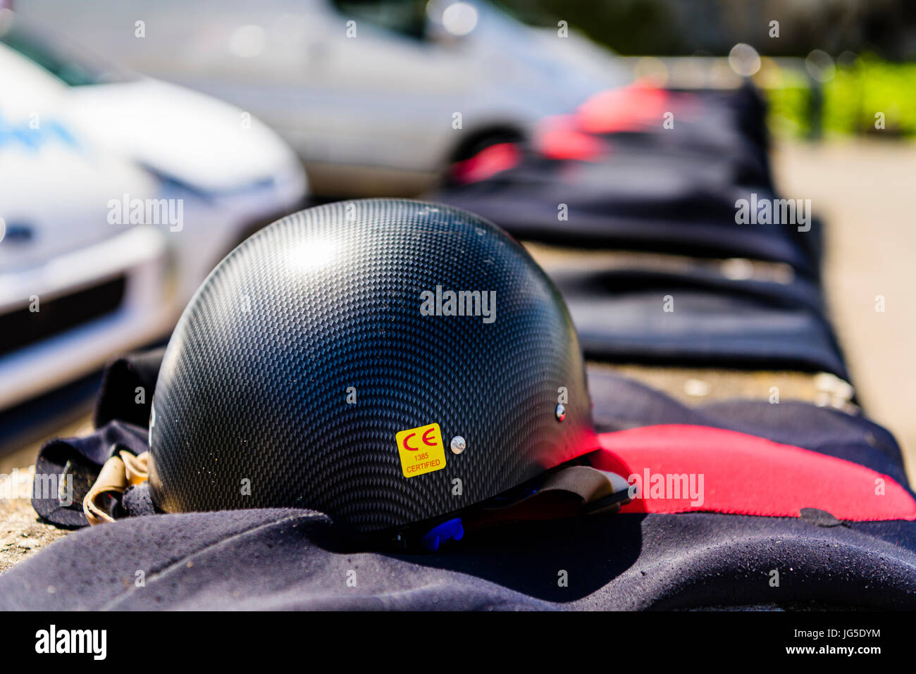 Safety helmet with wetsuits drying on a wall at a coastal car park. - Stock Image