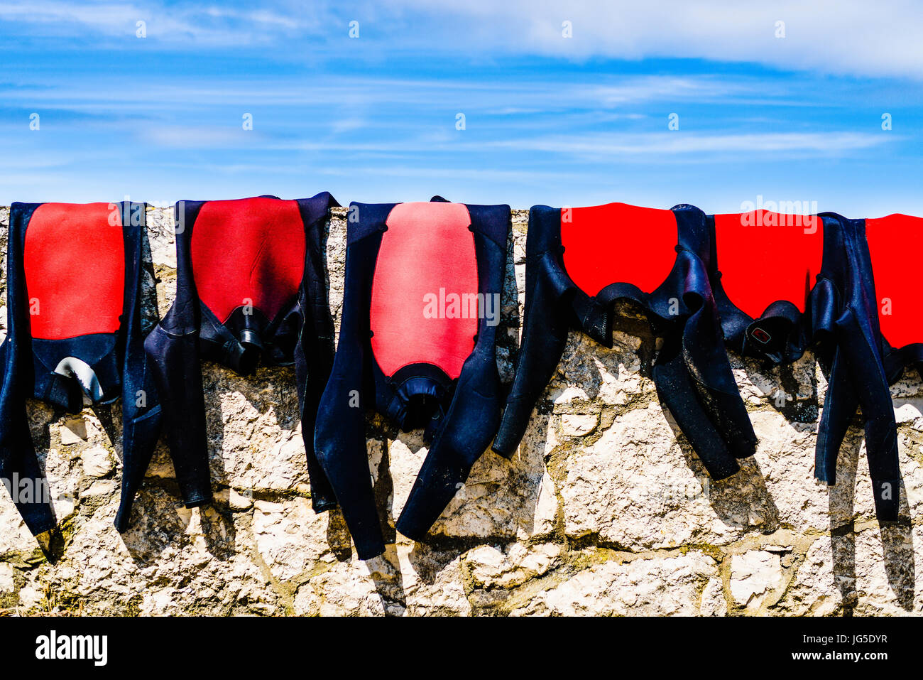 Wetsuits drying on a coastal stone wall. - Stock Image