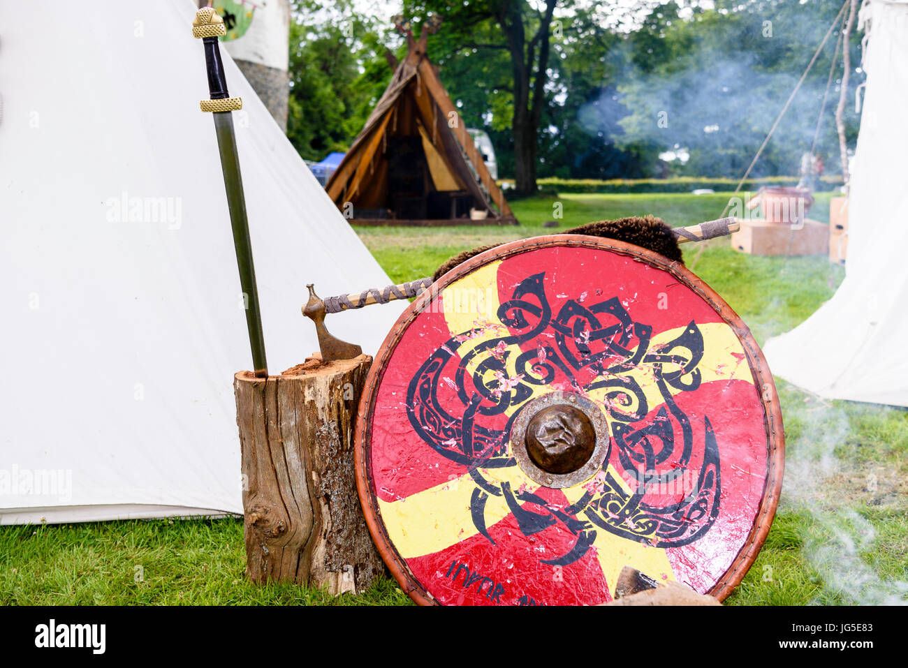 Sword, axe and shield belonging to a medieval soldier beside a fire at an army camp site. - Stock Image
