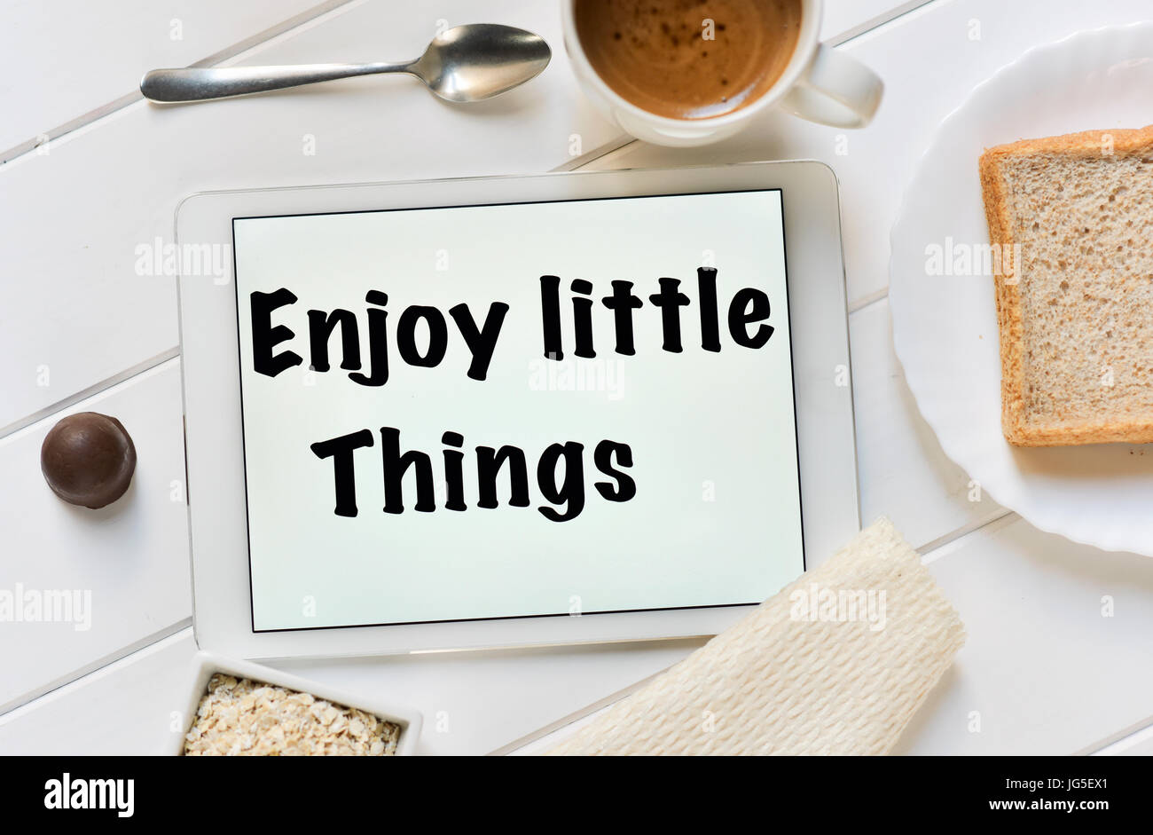 high-angle shot of a tablet with the text enjoy little things in its screen and a cup of coffee, a bowl with cereals - Stock Image