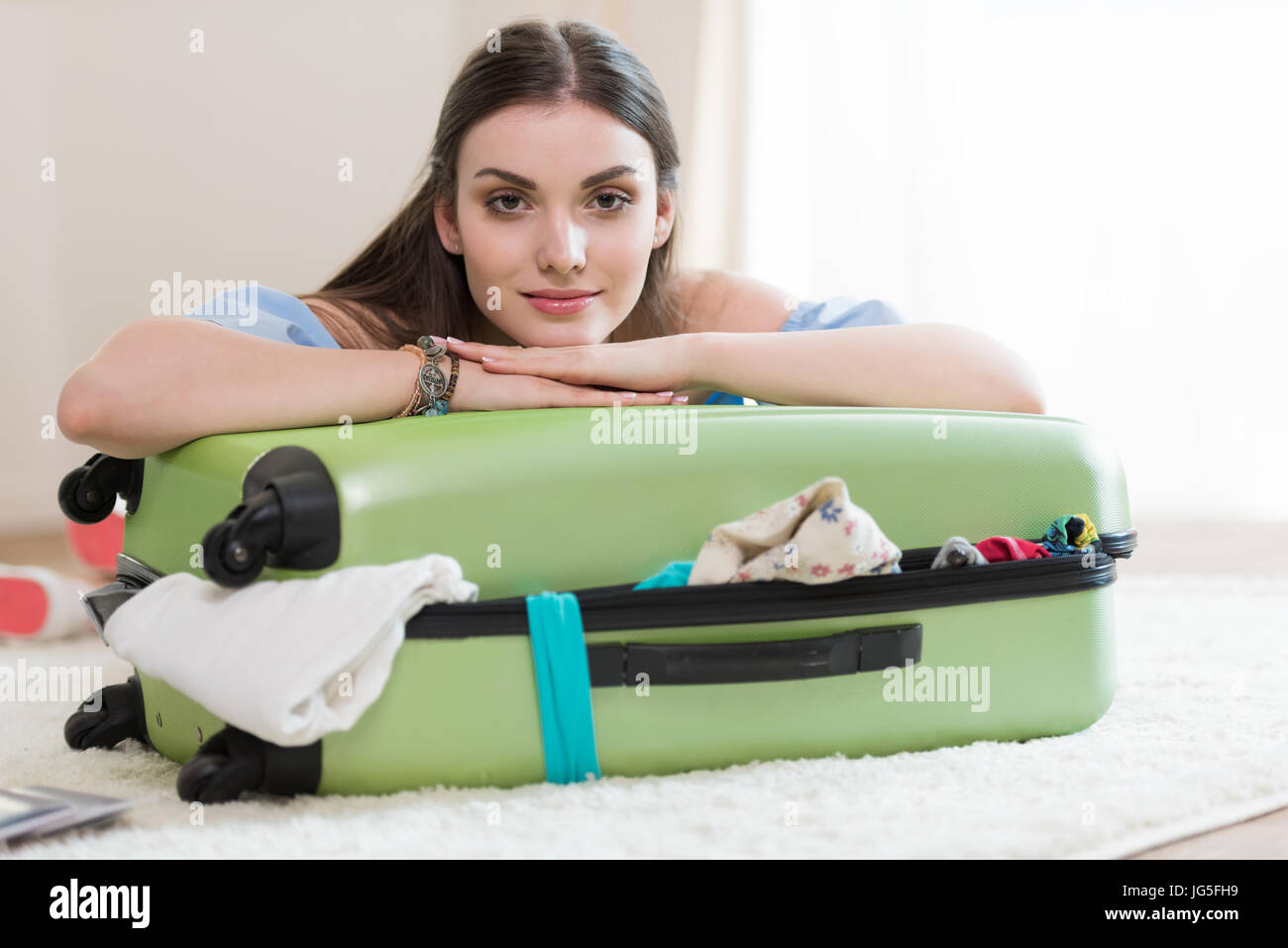 Beautiful young brunette woman packing suitcase and looking at camera, packing luggage concept - Stock Image