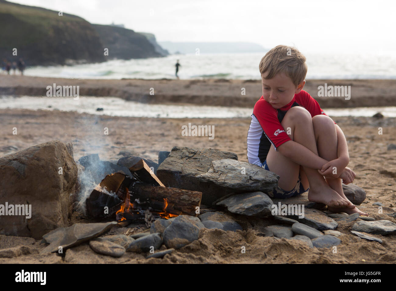 A boy watches over the beach fire on holiday, Cornwall, UK - Stock Image