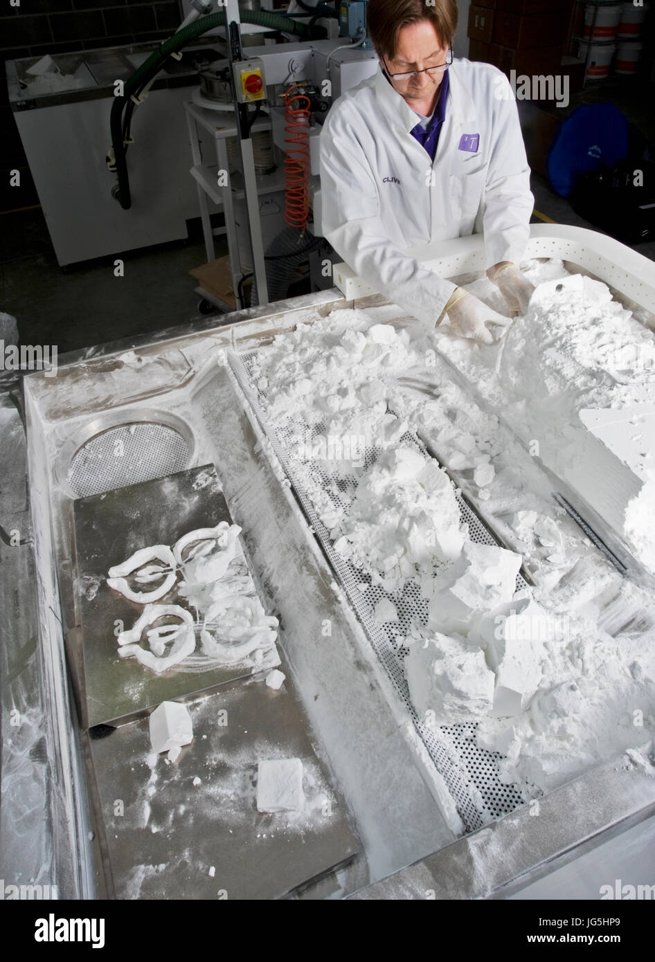 Unpolished prototype objects manufactured by the Selective Laser Sintering (SLS) process being released from the - Stock Image