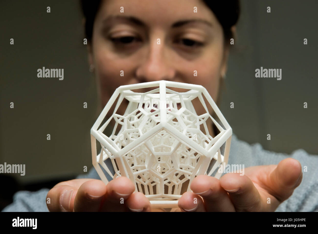 Woman holds complex 3-dimensional object produced by Selective Laser Sintering (SLS). - Stock Image