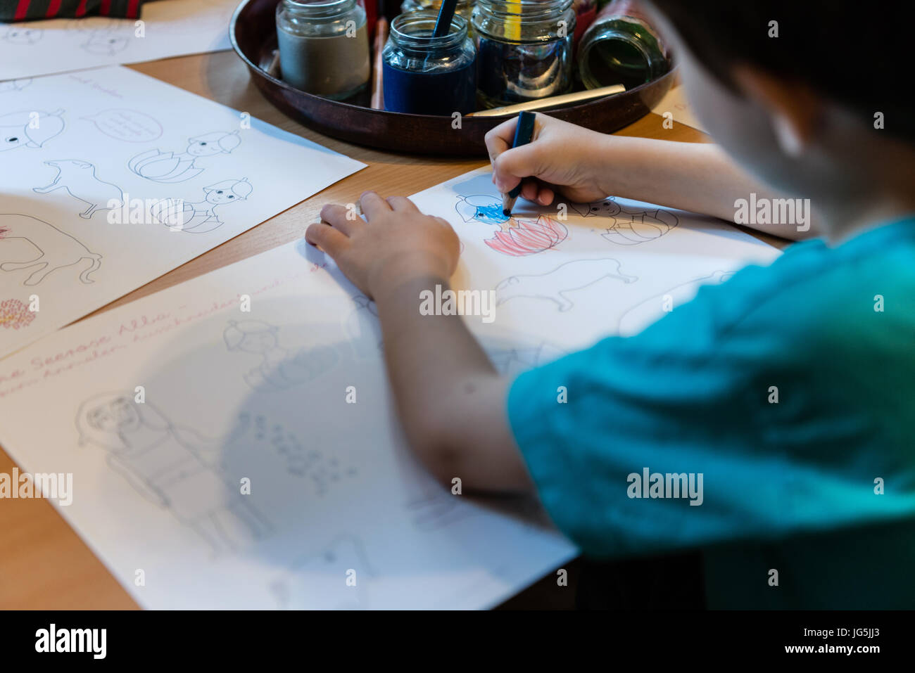 Child drawing with colored pencils in kindergarten, close-up - Stock Image