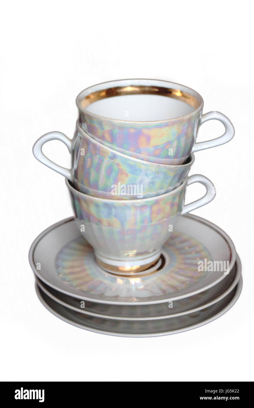 A pile of white iridescent tea cups and saucers - Stock Image