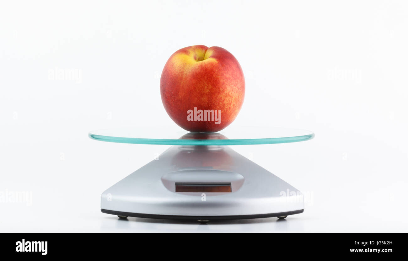 Fresh healthy peach placed on a digital electronic scale, sign of vegan lifestyle - Stock Image