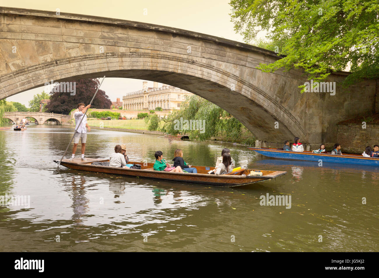 Cambridge punting - a punt passes under Kings Bridge, with Clare college in the  background; River Cam, Cambridge, - Stock Image
