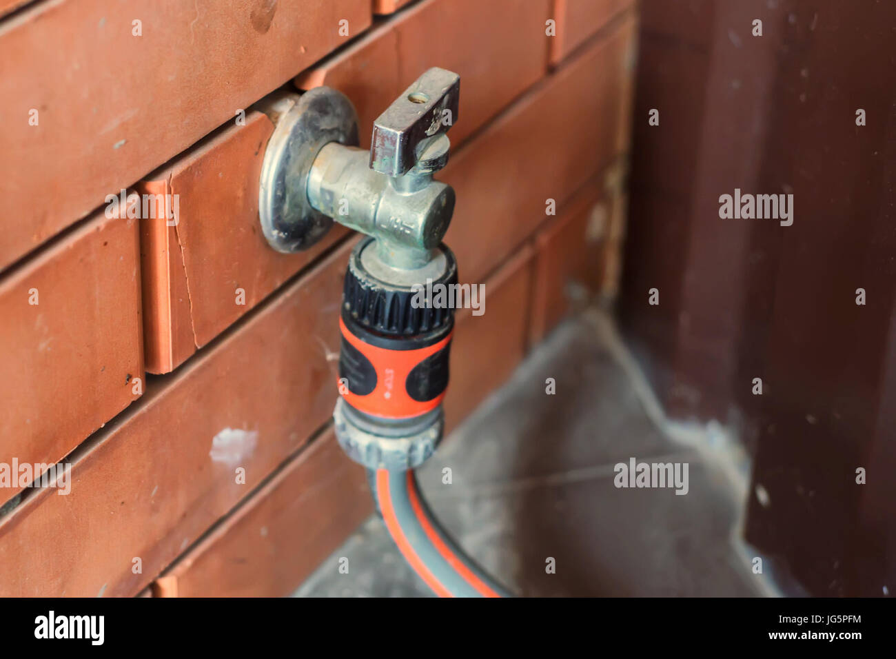 Garden tap with hose attached to it - Stock Image