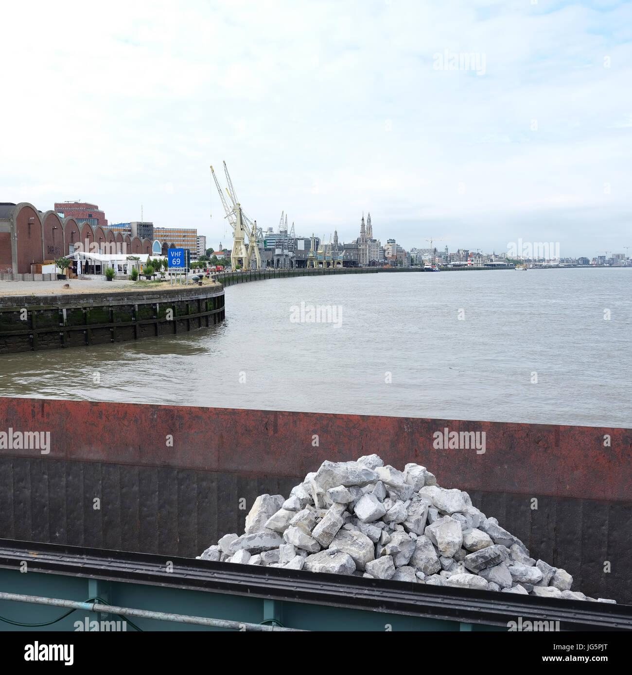 ship loaded with natural stone enters harbor on river Schelde in antwerp - Stock Image