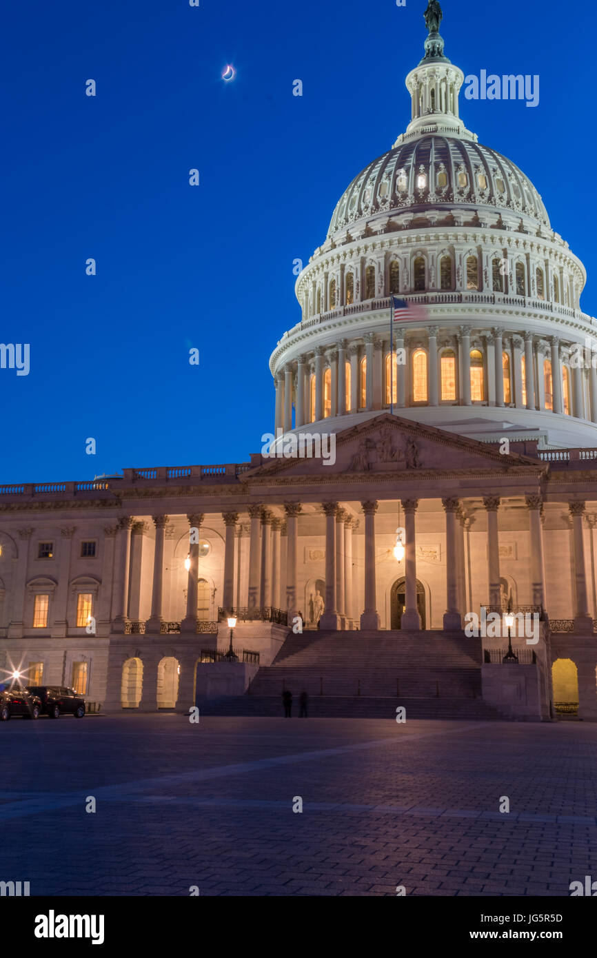 Moon Shining Above the US Capitol Building on a Clear Sky - Stock Image