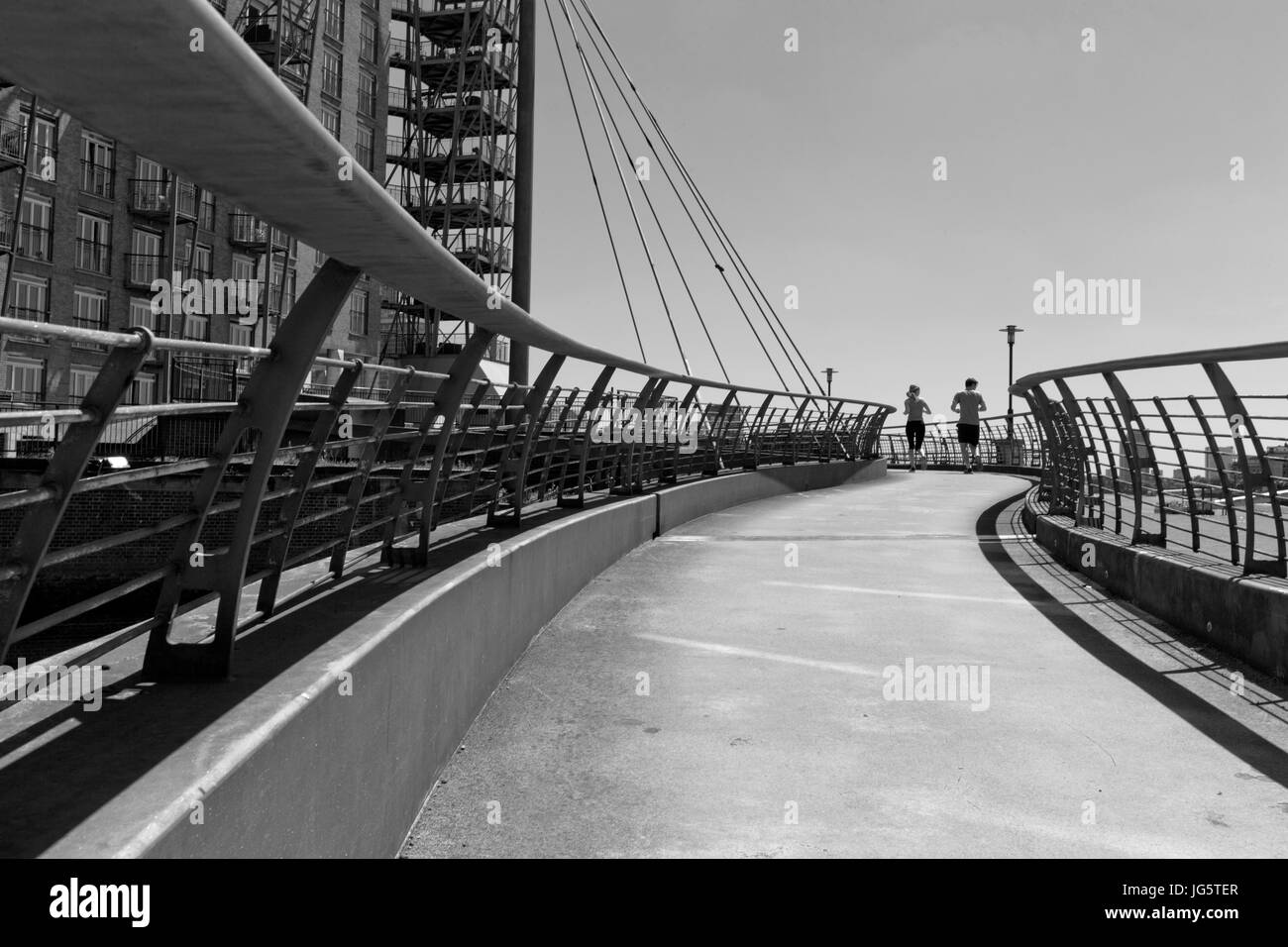 Two people running over a pedestrian bridge over an inlet of the river Thames, Narrow Street, Limehouse, Tower Hamlets, - Stock Image