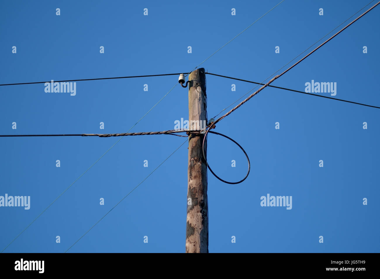 Low tension electrical pole on blue sky - Stock Image