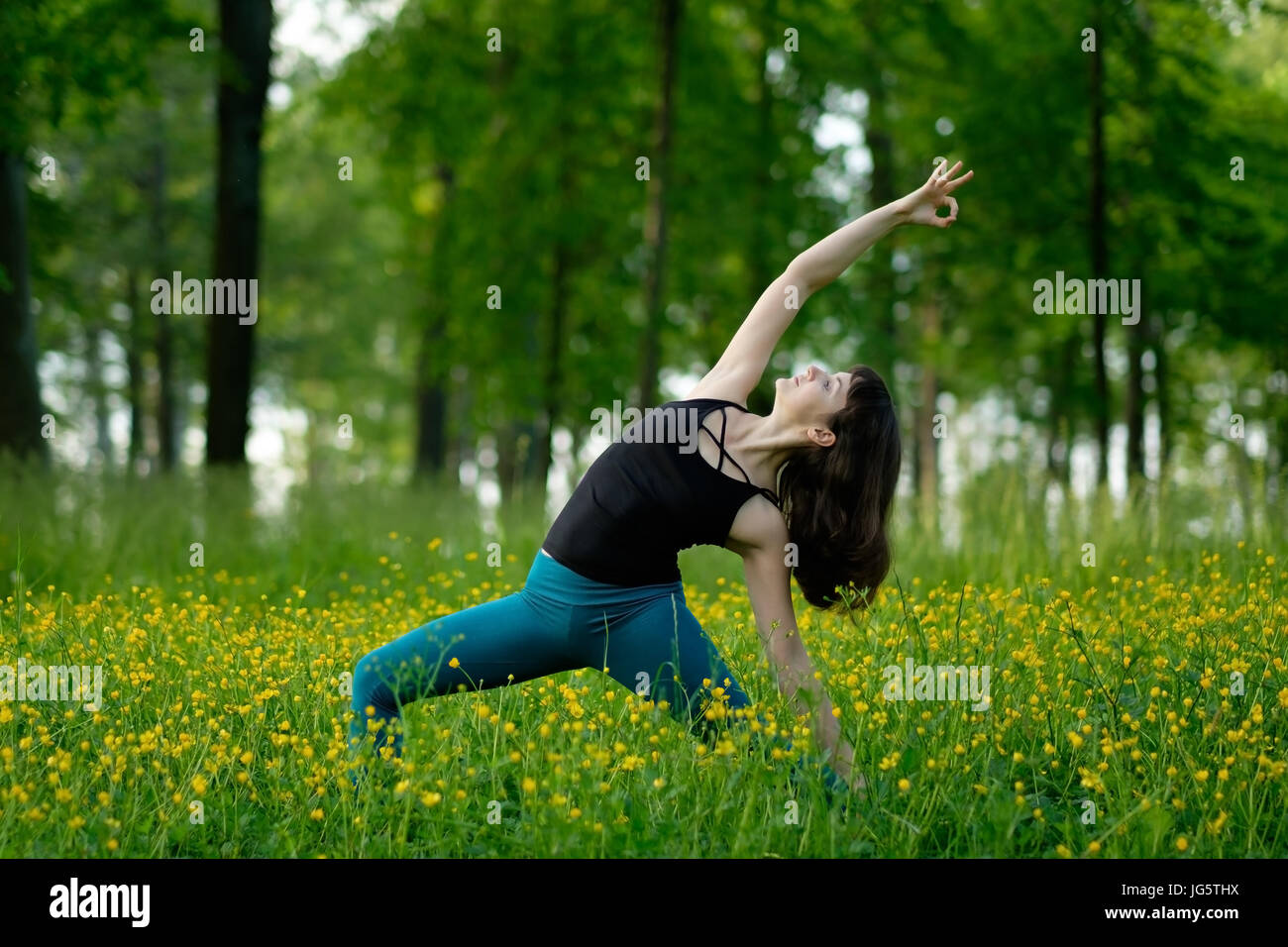 Young woman doing yoga on a green forest. - Stock Image