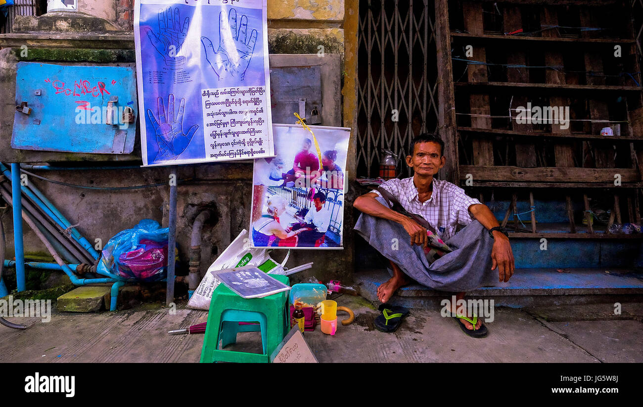 A man sits at his small street stall inYangon, Myanmar that specialises in providing hand massages - Stock Image