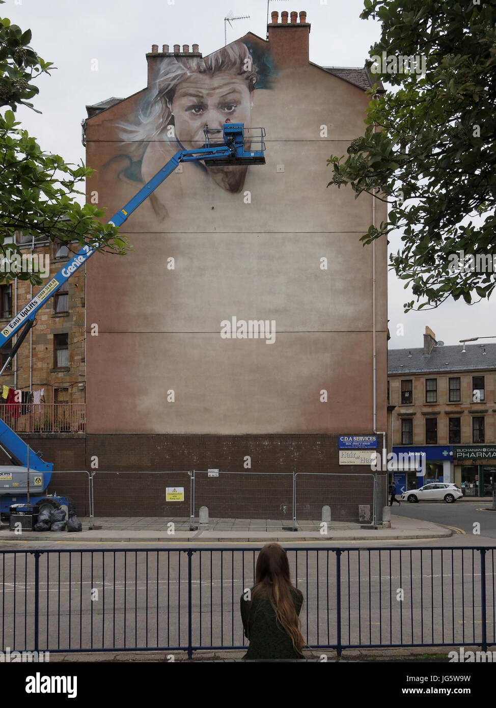 street mural being done for the 2014 Commonwealth games young girl possibly imagines herself as being the subject - Stock Image