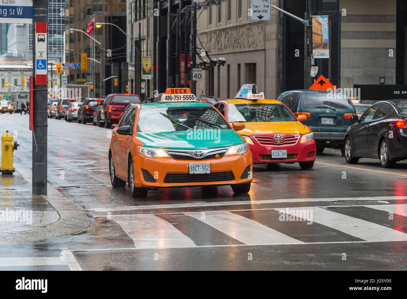 Toronto, Canada - 26 June 2017: 2 taxis in Downtown Toronto on a rainy day - Stock Image