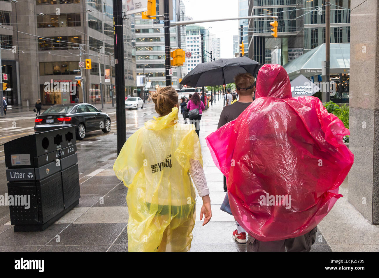 Toronto, Canada - 26 June 2017: Crowd of people with umbrellas and rain ponchos on a rainy day - Stock Image