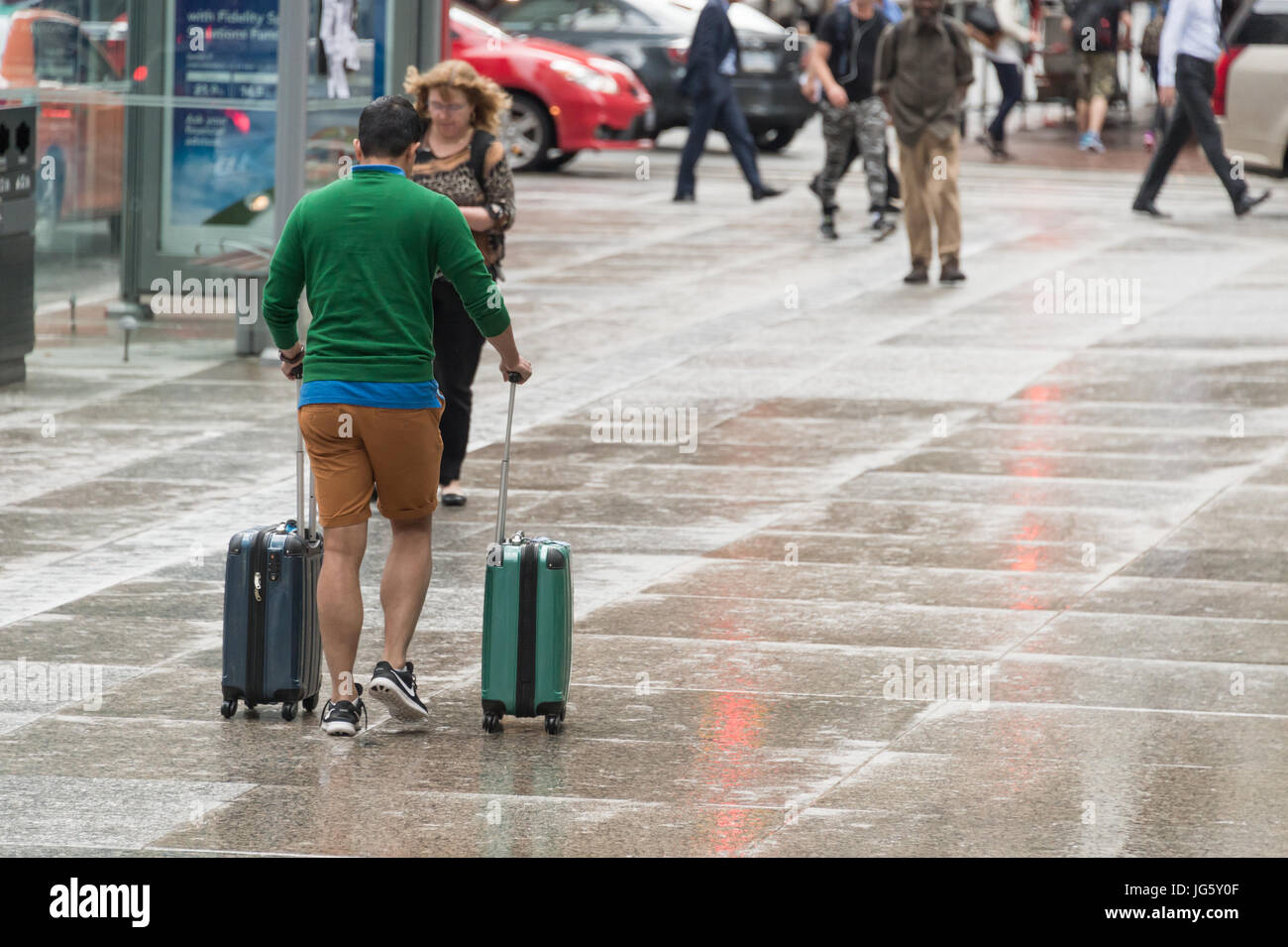 Toronto, Canada - 26 June 2017: Man with spinner luggage walking in Toronto Downtown on a rainy day - Stock Image