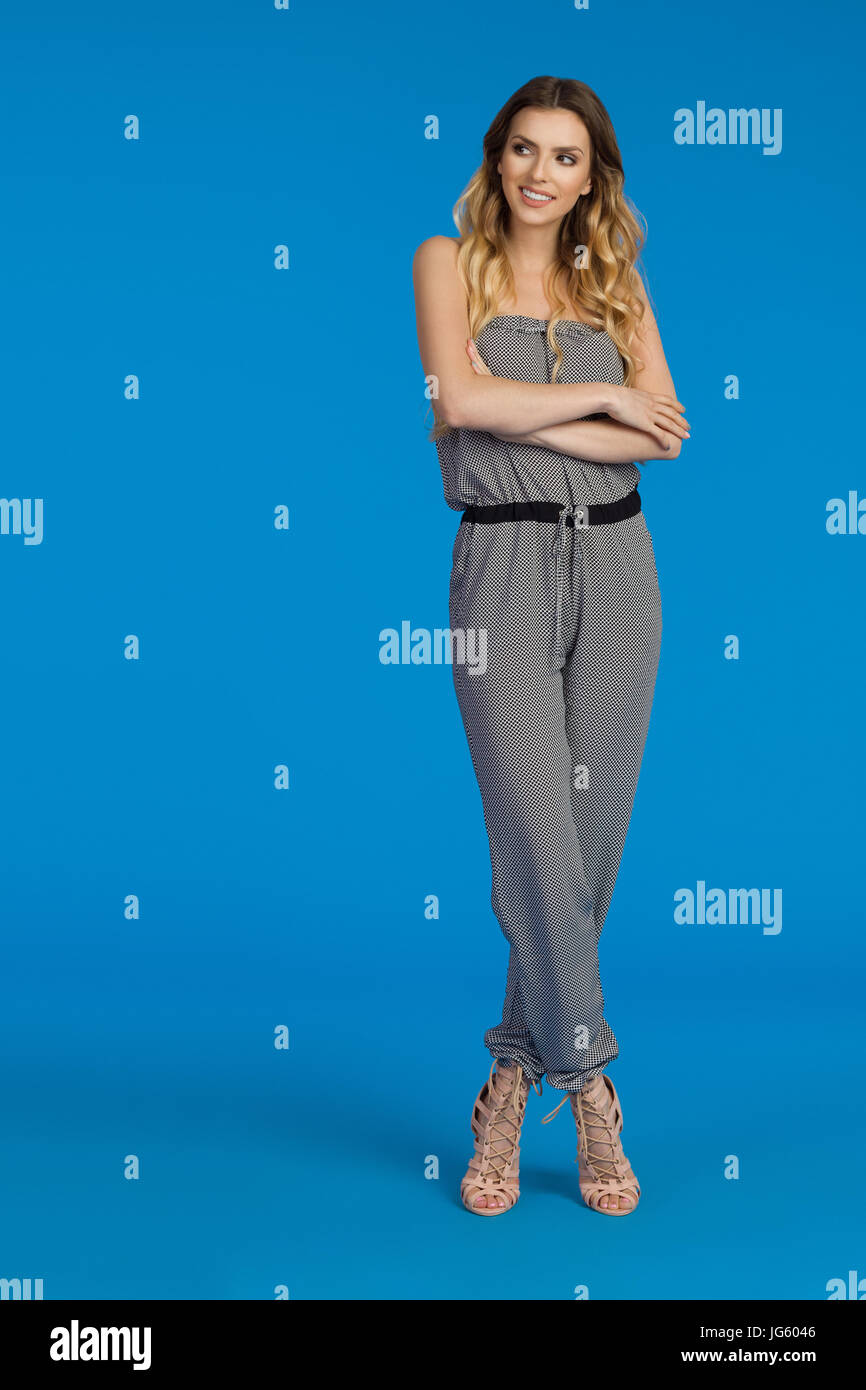 Beautiful young woman in dotted jumpsuit and high heels  is standing with arms crossed and looking away. Full length - Stock Image