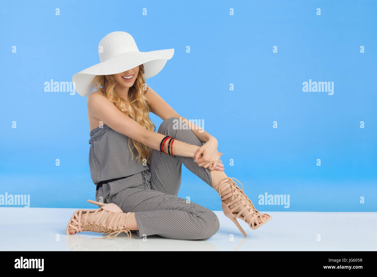 Young woman in summer jumpsuit, high heels and white sun hat is sitting on floor and smiling. Full length studio - Stock Image
