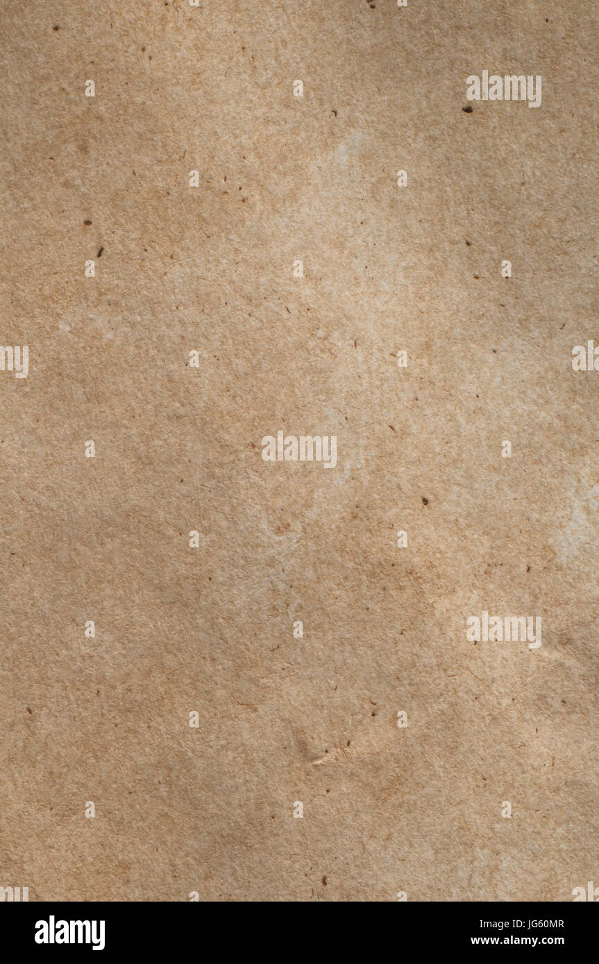 A piece of mid-toned fibrous, textured brown paper with scratches, fibres and flecks visible. - Stock Image