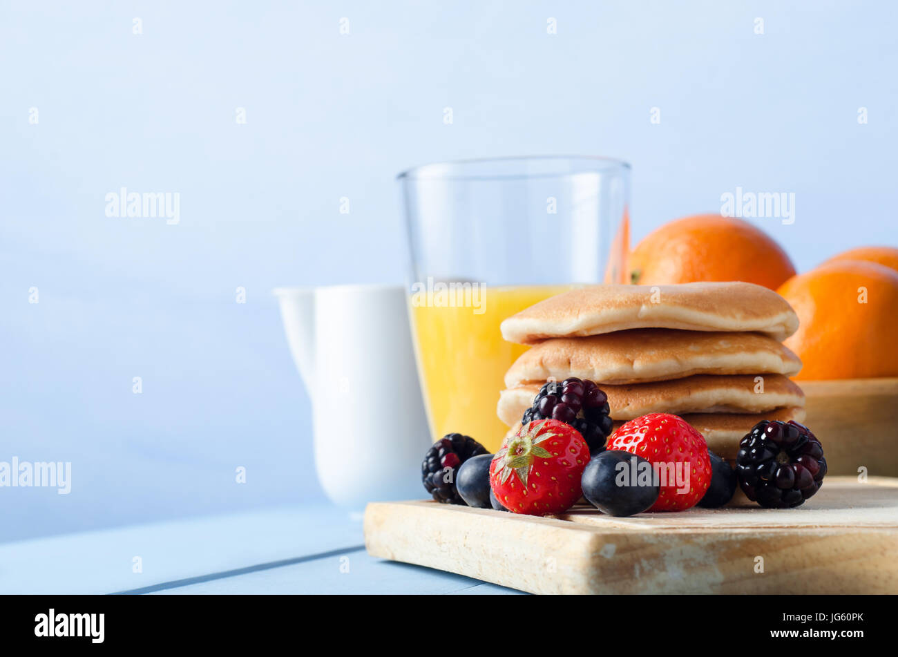 Breakfast table scene with Summer berry fruits and a stack of pancakes on an old wooden chopping board, a bowl of - Stock Image