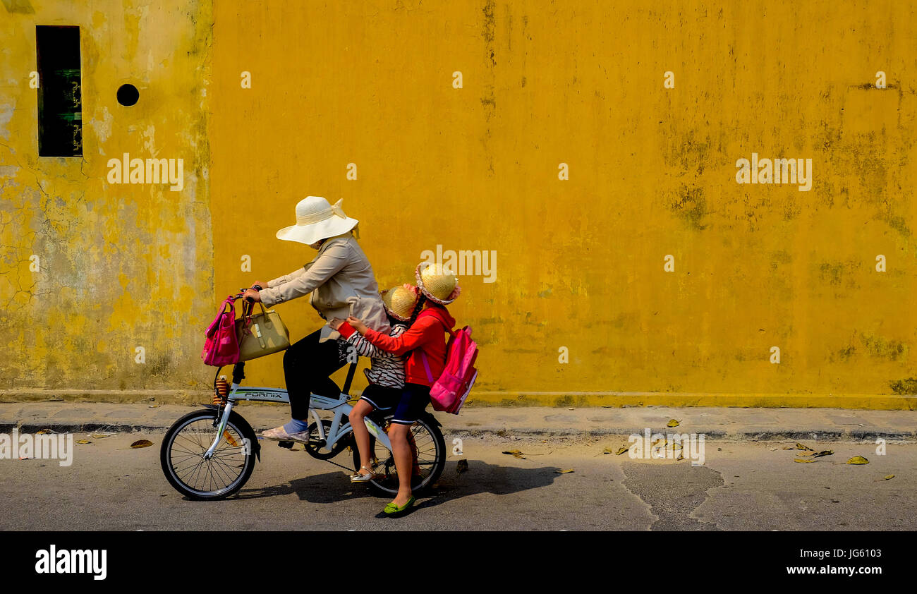 A woman rides a bike with two young children on the back in the Old Town of Hoi An, Vietnam - Stock Image
