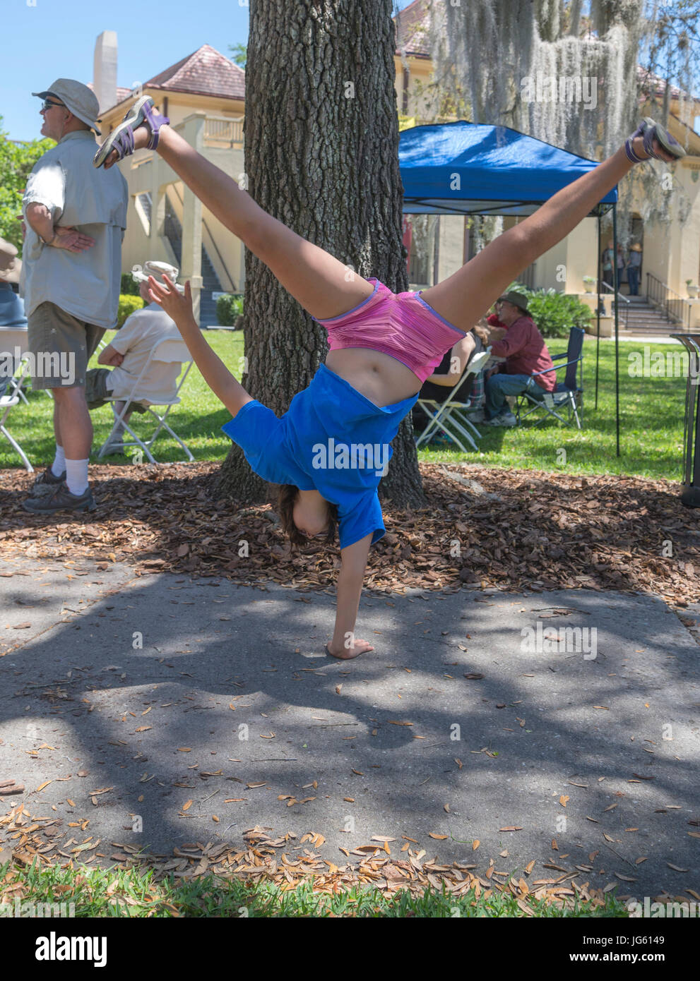 Girl does cartwheel at art festival. - Stock Image