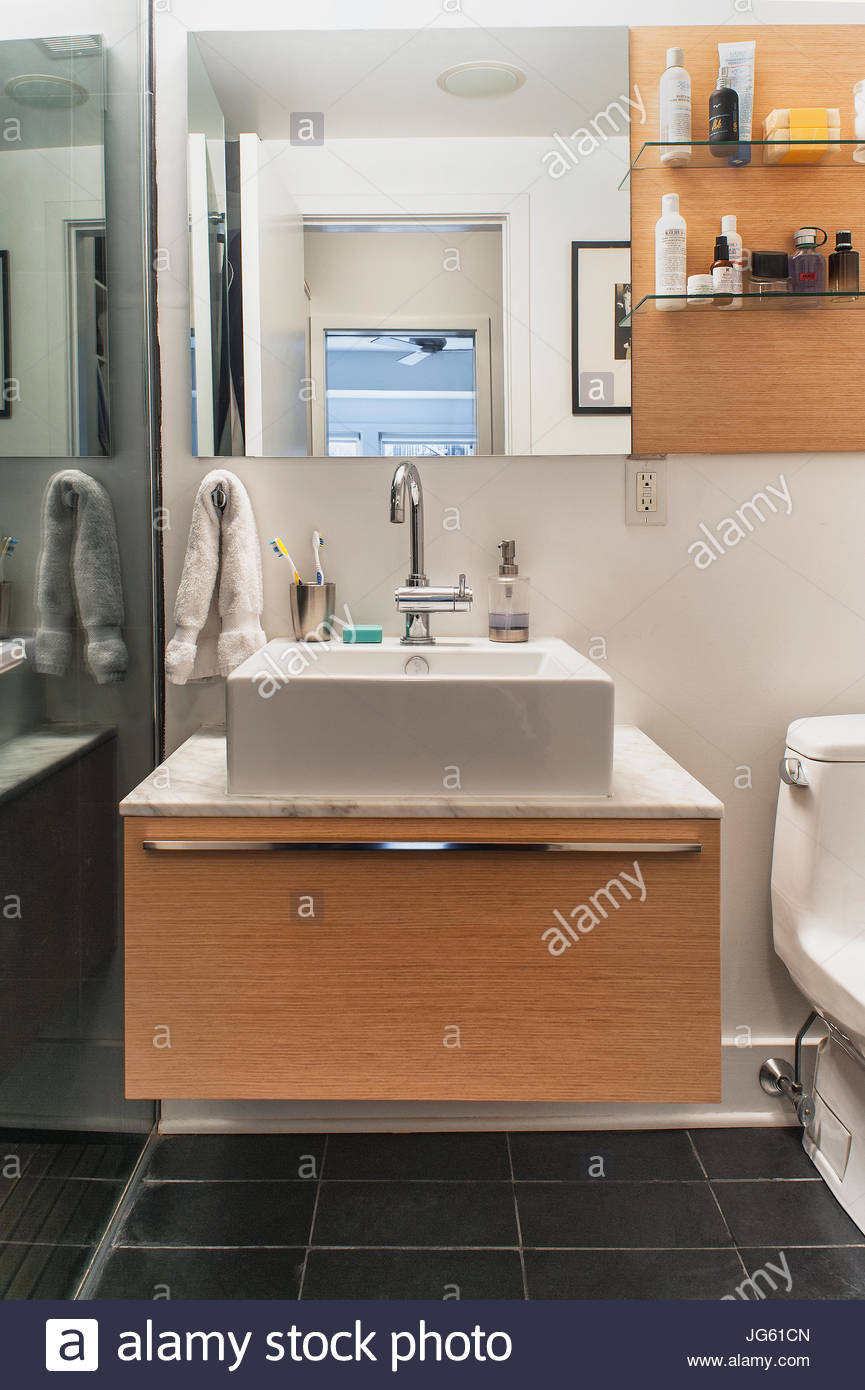 Modern bathroom with wall mounted sink, mirror, open shelving, grey ...