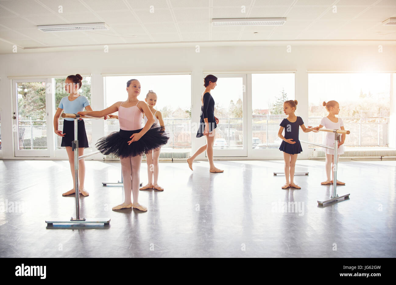 Young girls performing ballet standing and exercising in ballet class. - Stock Image