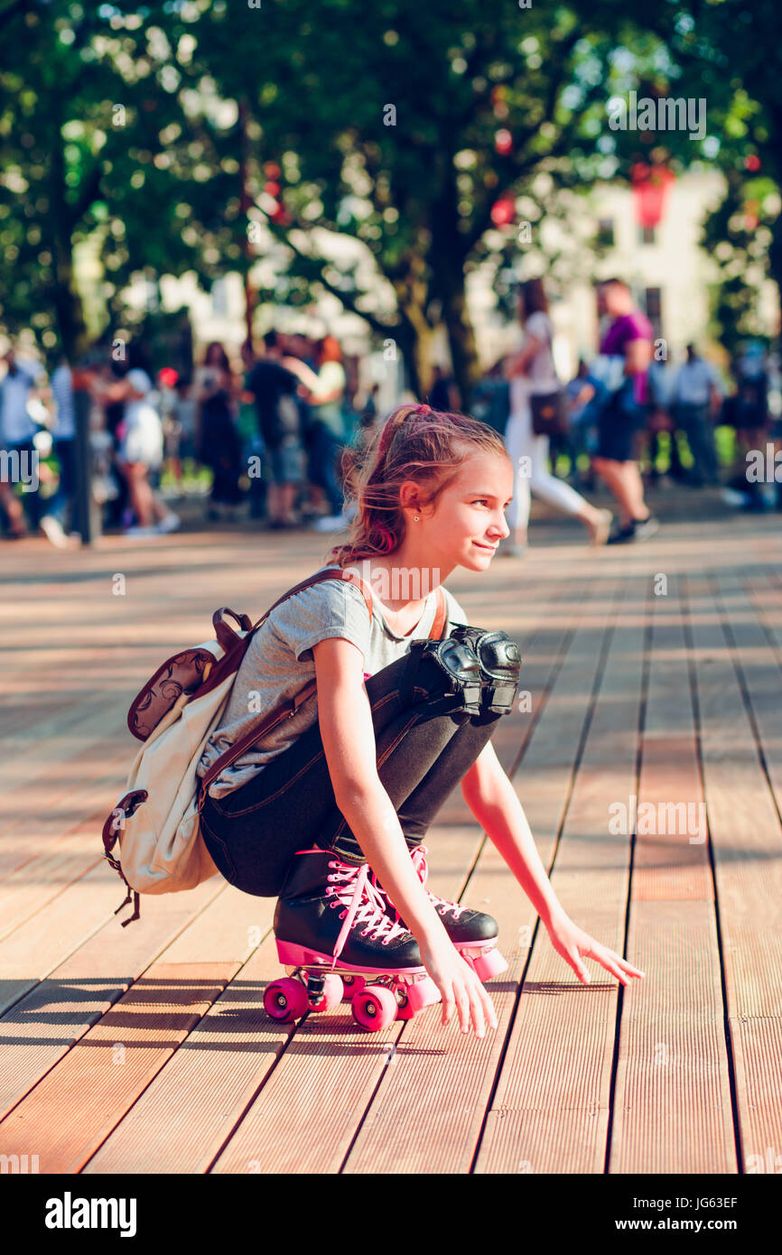 Young girl roller skating in a town spending time actively outdoors on summer day - Stock Image